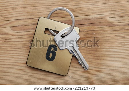 Hotel suite key with room number 6 on wood table  - stock photo