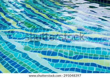 Hotel swimming pool with sunny reflections - stock photo