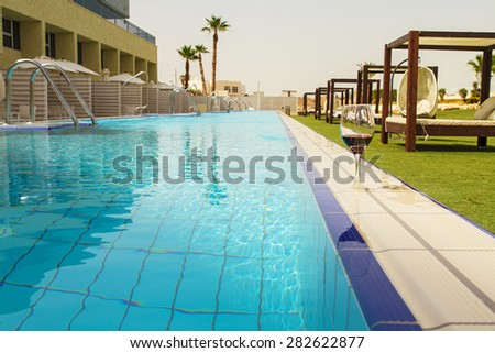 Hotel swimming pool with sunny reflections and a glass of wine . - stock photo
