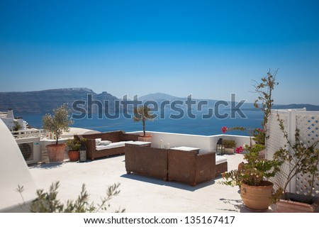 Hotel terrace with sofas . Beautiful view at the seaside. Santorini, Greece. - stock photo