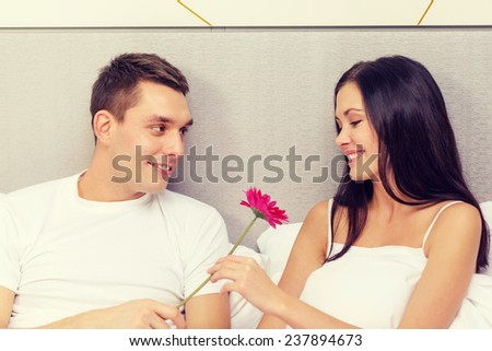 hotel, travel, relationships, holidays and happiness concept - smiling couple in bed with pink flower - stock photo