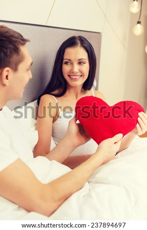 hotel, travel, relationships, holidays and happiness concept - smiling couple in bed with red heart-shaped pillow - stock photo