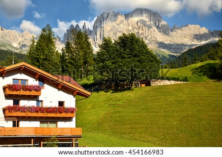 Hotel under Dolomite in italy for tourist surrounded in green nature and blue sky. Europe - stock photo