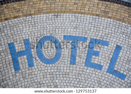 Hotel written in mosaic in front of the entrance - Paris, France. - stock photo