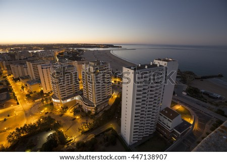 Hotels and beach at the bank of the ocean during sunrise. View from above. Pria Da Rocha, Portimao, Portugal. - stock photo