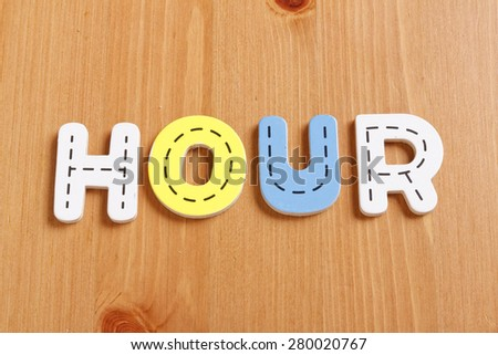 HOUR, spell by woody puzzle letters with woody background - stock photo