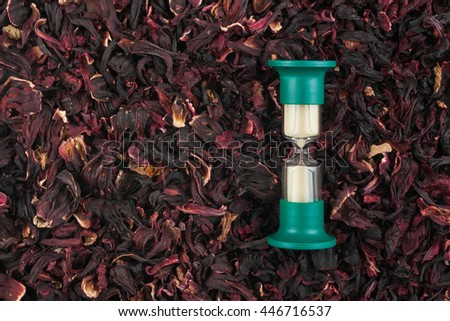 Hourglass and the dried Hibiscus, a conceptual time and food - stock photo