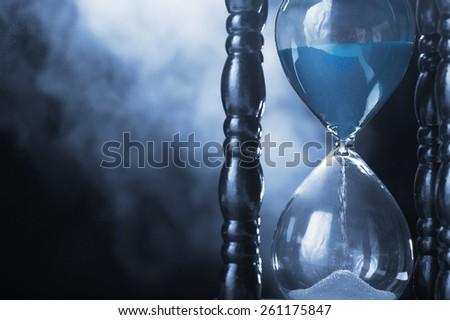 Hourglass clock and smoke on dark background - stock photo