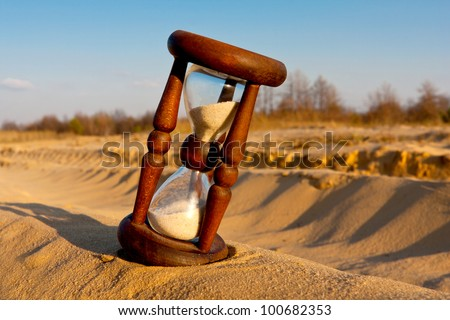 hourglass in desert's sand - stock photo