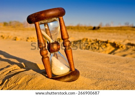 hourglass in desert sandy surface - stock photo