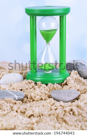 Hourglass in sand on bright background - stock photo