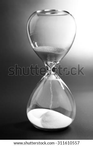 Hourglass on dark background - stock photo