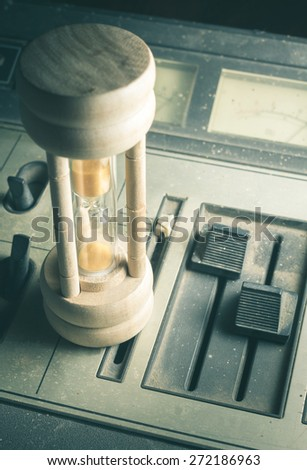 Hourglass on retro sound player or mixer,vintage filtered. - stock photo