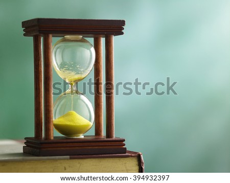 hourglass on top of book in front of black board - stock photo