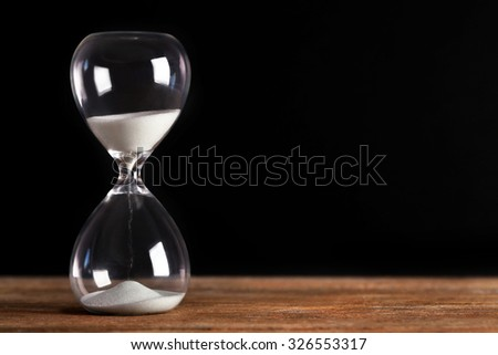 Hourglass on wooden table on black background - stock photo