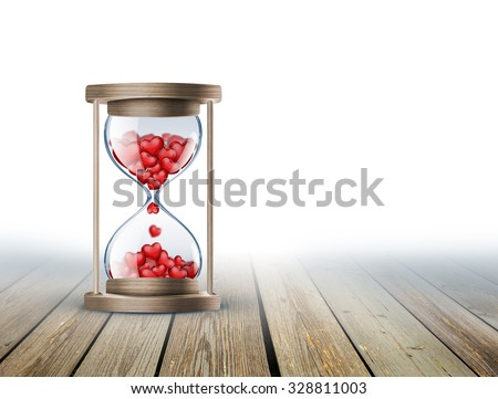 hourglass with red hearts on wooden surface - stock photo