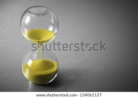 Hourglass, Yellow Sand on Stainless Steel - stock photo