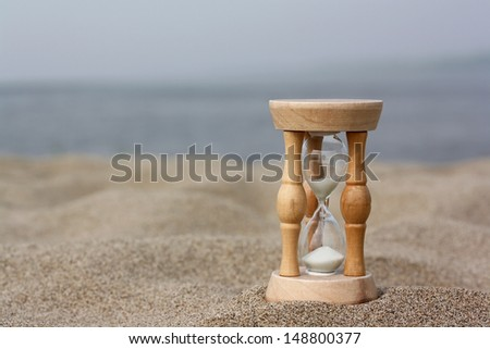 Hourglasses against sandy beach and sky - stock photo