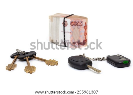 House and car key with pile of rolled cash money white background - stock photo