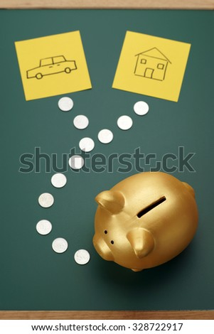 House and car savings - golden piggy bank, coins and house and car sketch - stock photo