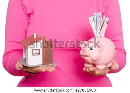 House and pink piggy bank in a female hands - stock photo