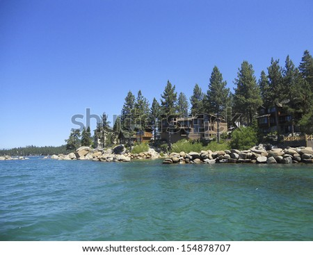 house and trees on a lake - stock photo