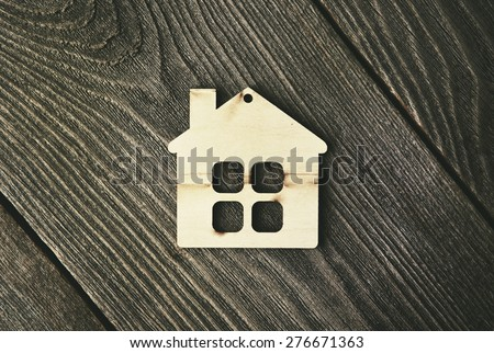 house as symbol on wooden background - stock photo