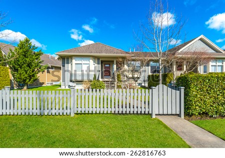 House behind country style long wooden fence with nicely trimmed grass. - stock photo