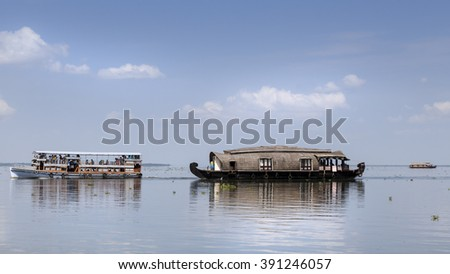 House boats on the Kerala Backwaters in southern India with reflections and white clouds in a bright blue sky - stock photo