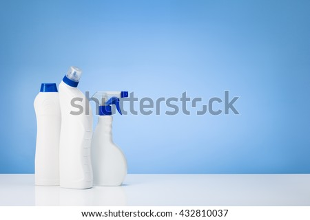 House cleaning products on white table with blue gradient backdrop. Lots of copy space around objects. - stock photo