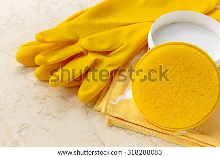 House cleaning tools -  rubber gloves, cleaning cloth, sponge and house cleaning cream on marble. - stock photo