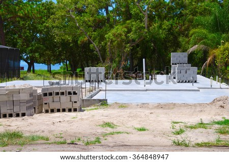 House construction concrete foundation with plumbing pipes sticking up, concrete cinder blocks are in stacks in preparation for building the walls of the home. - stock photo