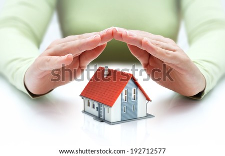 house covered of woman hands - protect and insurance real estate concept  - stock photo