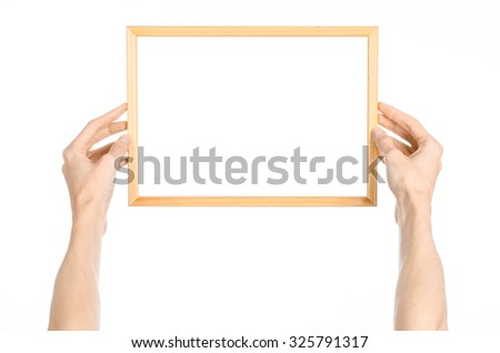 House decoration and Photo Frame topic: human hand holding a wooden picture frame isolated on a white background in the studio first-person view - stock photo