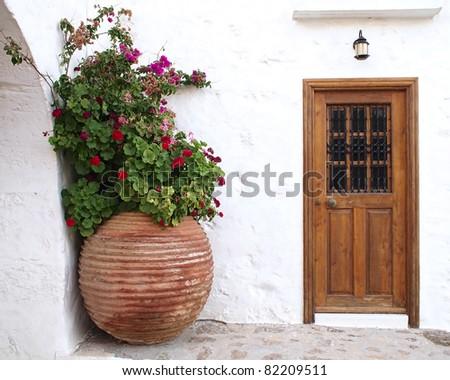 house door and huge flower jar, Greece - stock photo