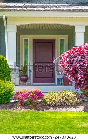 House entrance with nicely trimmed and landscaped front yard. - stock photo