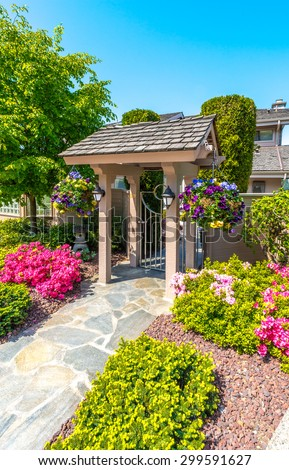 House entrance with the paved doorway the door and nicely trimmed and landscaped front yard. Vertical. - stock photo
