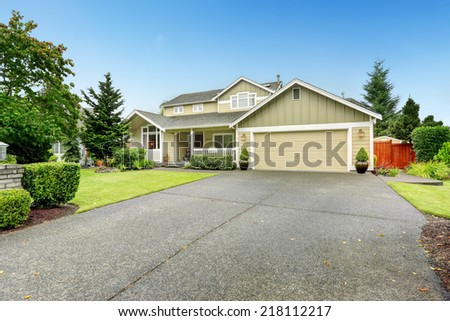 House exterior. Spacious walkout deck with railings. Garage with driveway - stock photo