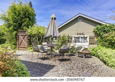 House exterior with backyard deck. View of patio table set with umbrella - stock photo