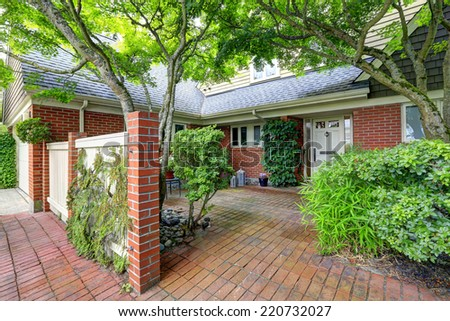 House exterior with brick trim and fence. - stock photo