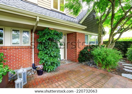 House exterior with brick trim and tile floor - stock photo
