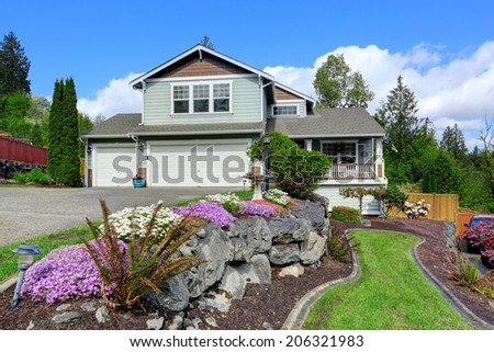 House exterior with curb appeal. View of entrance porch, garage and driveway. Beautiful front landscape - stock photo