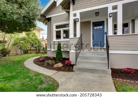 House exterior with entrance porch. View of staircase and front yard landscape - stock photo