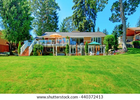 House exterior with impressive backyard landscape design and cozy patio area. - stock photo