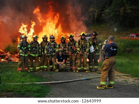 House fire with a group of firefighters getting their photo taken in front of the fire - stock photo