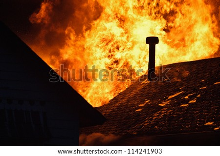 House fire with heavy flame, glowing roof and chimney. - stock photo