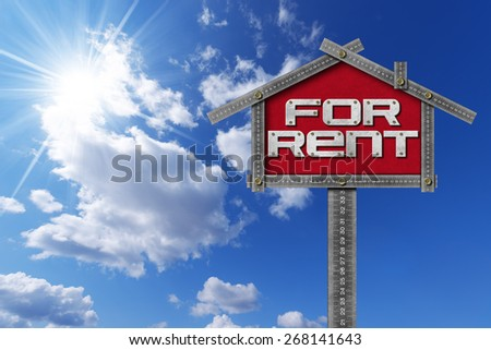 House For Rent Sign - Metallic Meter. Grey metallic meter ruler in the shape of house with text for rent. For rent real estate sign on blue sky with clouds and sun rays - stock photo
