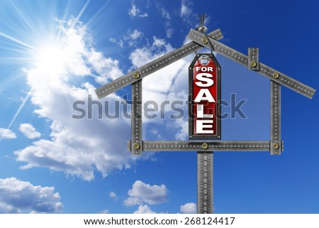 House For Sale Sign - Metallic Meter. Grey metallic meter ruler in the shape of house and label with text for sale. For sale real estate sign on blue sky with clouds and sun rays - stock photo
