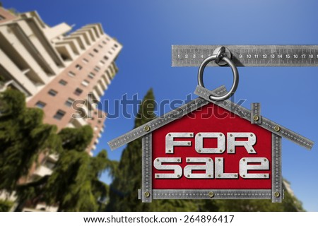 House For Sale Sign - Metallic Meter. Grey metallic meter ruler in the shape of house with text for sale. For sale real estate sign with tall and blurred buildings in the background - stock photo