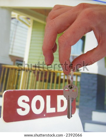 House for sale with sold sign and hand holding a key - stock photo